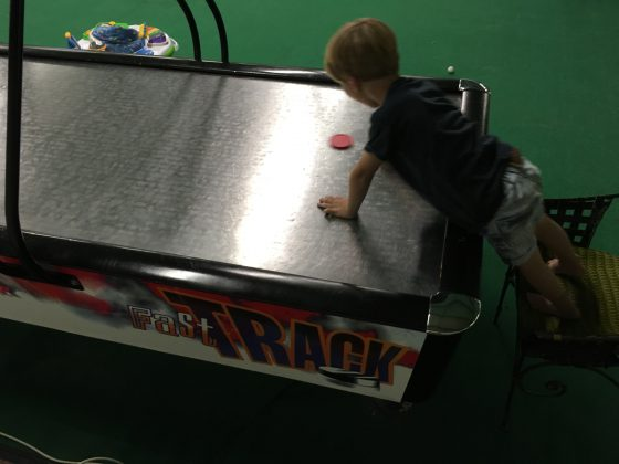 The boy's first game of air hockey. He thought it was hilarious every time he let a goal in!
