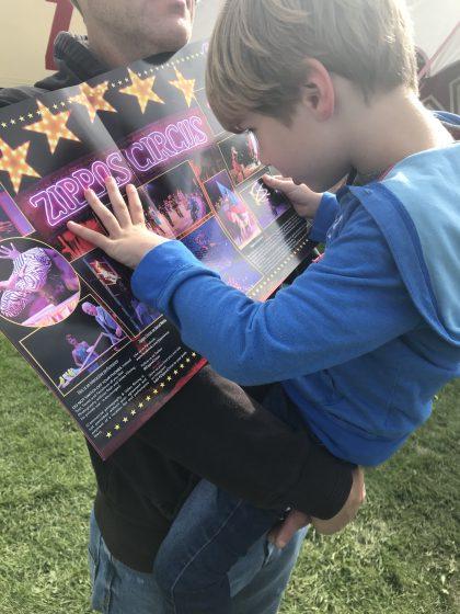 small boy reading circus programme